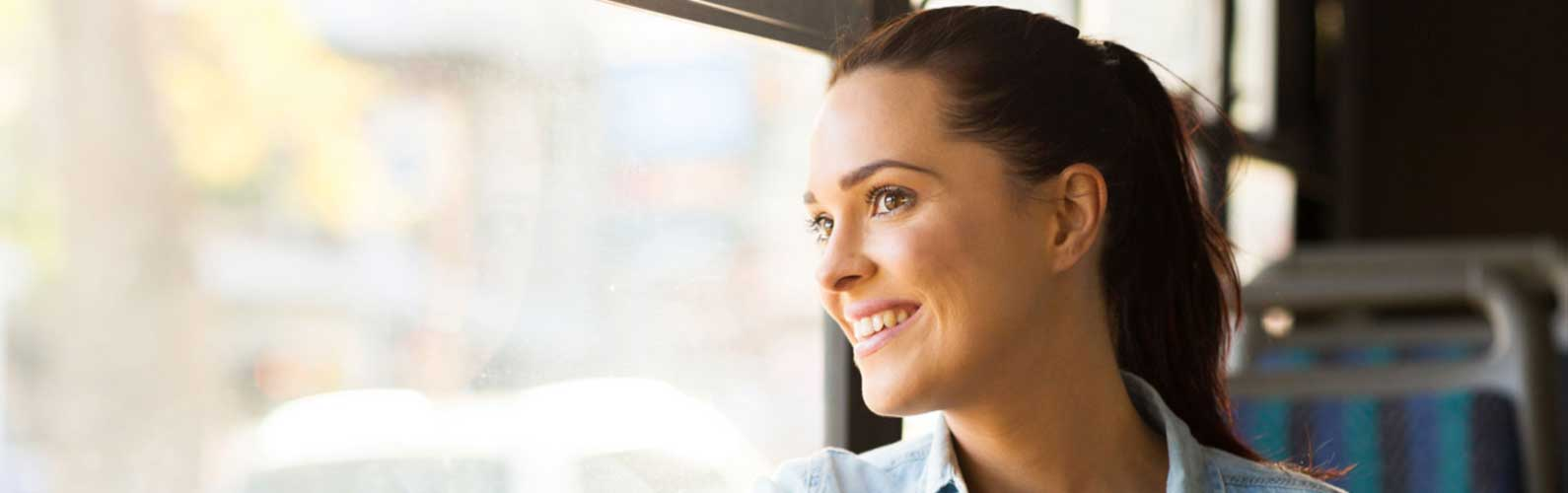A woman smiles while riding the EC Rider Bus